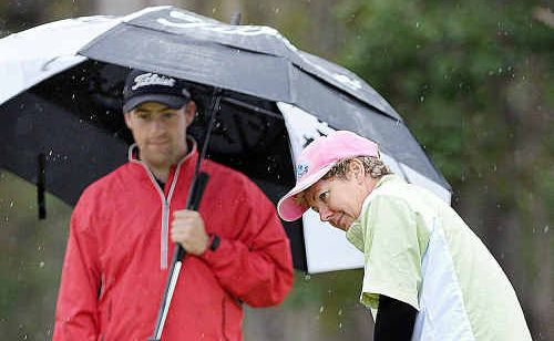 Professional Timothy Porter does his best to stay dry as Donna Burraston putts during the annual Burrum District Golf Club Pro am on Saturday.
