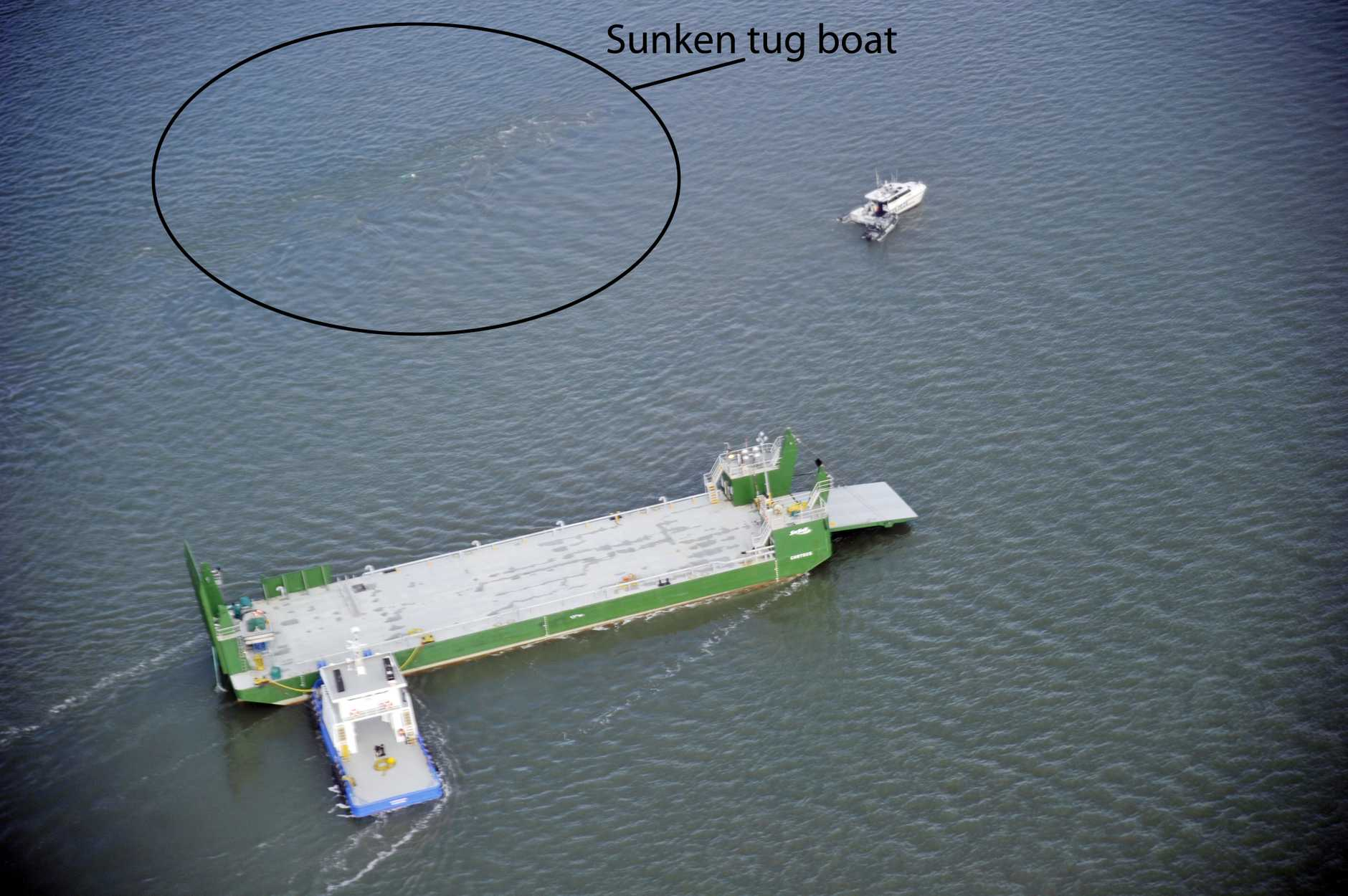 The tug boat was towing this water barge when it capsized and sank. The water can be seen rippling above the sunken tug boat.