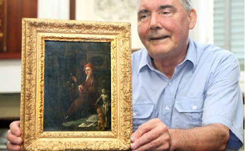 Maryborough Wide Bay and Burnett Society assistant Edward Mosig shows the painting that's estimated to be worth about $1 million and dated about 1731.