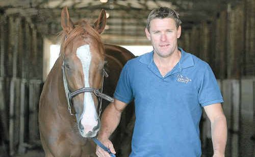 Horse trainer Stephen Rundle leads Harvzee from the stable at Callaghan Park after the horse gave him his first career win on Saturday.