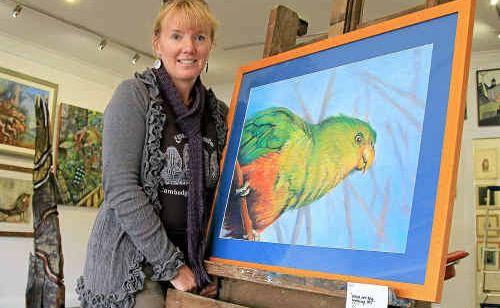 Artist Julianne Gosper displays one of her paintings .
