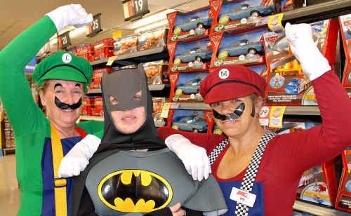 Mackay Kmart staff, from left, Sharon Pelayo, as Luigi, Nicole Doolan, as Batman, and Viv Burton, as Mario, play dress up during the toy sale.