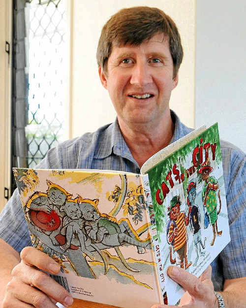 Daniel Hevenor with his children's book titled Cats in the City.