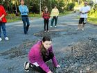 Kristy Goldsby and neighbours check out Avocado Heights potholes.
