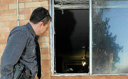A detective looks into the house where a suspected speed lab was found yesterday.