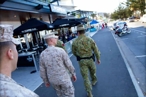 US Marine Staff Sgt Joseph Ross (right) and Lance Corporal Christopher Jones, follow Australian Corporal Timothy Newely (left) and Corporal Sam Preston-Stanley strolling the beachfront of Yeppoon.