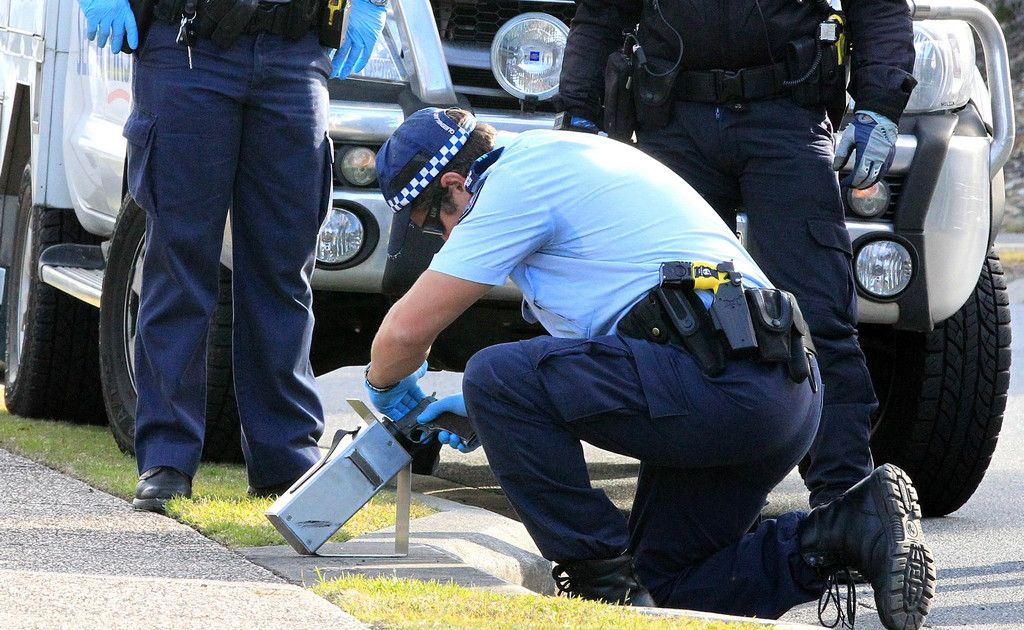 Police recover the semi-automatic pistol used at the Dog and Parrot Tavern at Robina from a storm water drain.