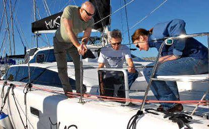 Skipper and owner of Muskat 1, Dr Nils Wagner, left, Dr Bert Sadleir and Alex Josephson prepare the catamaran for their humanitarian voyage to Papua New Guinea in September.