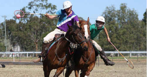 Emerald Polocrosse player Ben Brazier controls the ball, marked up hard by Jess Taylor from the Bauhinia.