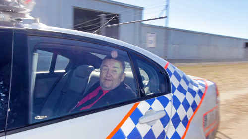 Peace activist Bryan Law being taken away in a police car from Rockhampton Airport after he damaged an Australian helicopter.