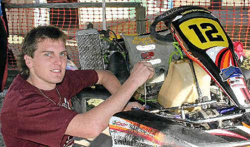 Warwick driver Brett Sinkins works on his kart at the Sandy Creek Raceway yesterday.
