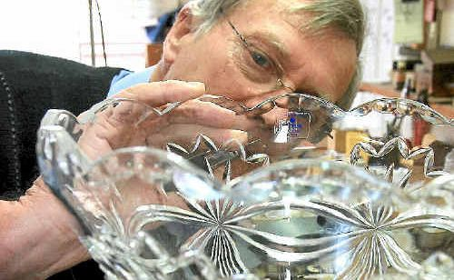 Lawrence Anderson puts the finishing engraving touches on the Daily News Cup.