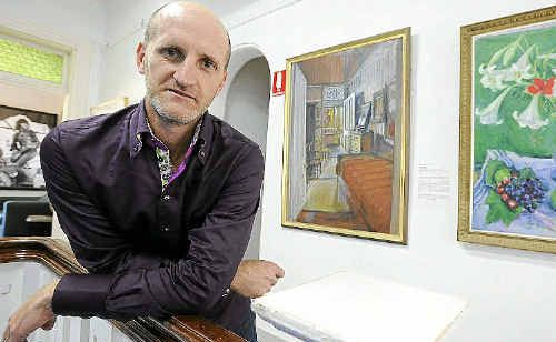 Lismore Art Gallery Director Brett Adlington with two Margaret Olley paintings that are part of the permanent collection.