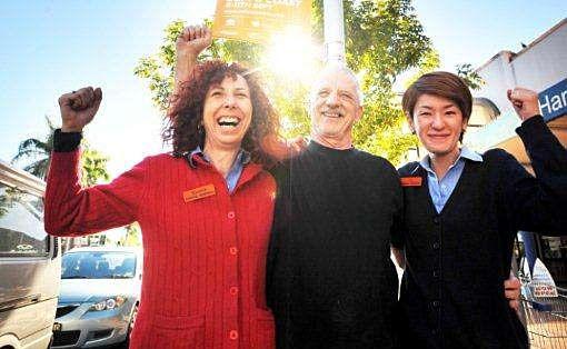 RALLY CHEERS: Maureen Burgess, left, Rex Madigan and Eri Chimatsu in Harbour Drive on Wednesday.