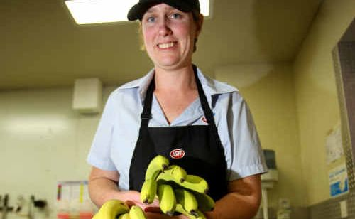 Susan Hall keeps the banana stand well stocked at the Glenmore IGA this week.