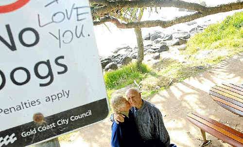 Les and Pat Draper under some the romantic but anonymous graffiti that has mysteriously popped up in Coolangatta and Rainbow Bay.