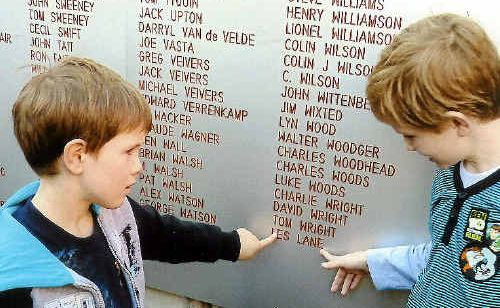 William and Thomas Lane point to the name of their grandfather Les Lane outside Suncorp Stadium.