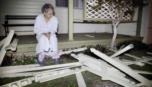 Red Rock resident Lois Russell inspects the damage after a car crashed into the front yard of her home on Tuesday night, while (inset) police allege the Ford Falcon driver fled the crash scene.
