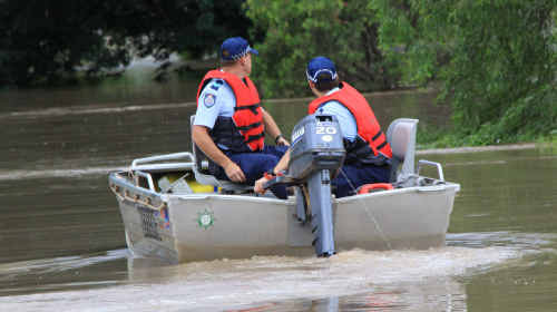 Police patrol rising floodwaters in Emerald.
