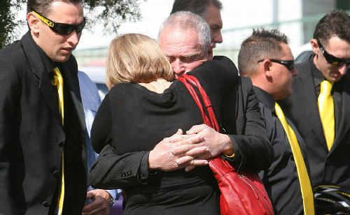 Narelle Dobinson's family comfort each other after her funeral service.