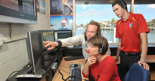 Premier Anna Bligh checks out the Parkyn Parade lifeguard command centre. Showing her the ropes are lifeguard Beau Farrell (left) and Surf Com operator Sebastian DePaula.