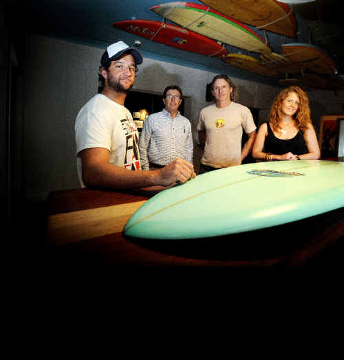 Pictured with a Michael Peterson surfboard to raise money for Aussies for Orphans, are from left, co-owner of Woodys Surf Shack in Byron Loren Nowland, Steve Lewis from Aussies for Orphans, surfboard shaper Simon Jones and co-owner of Woodys Caitlin Leiweke .