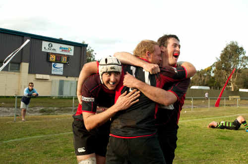 Will Guest (left) celebrates scoring the final try of the rugby grand final with Kris Kent and Dylan Hurley.