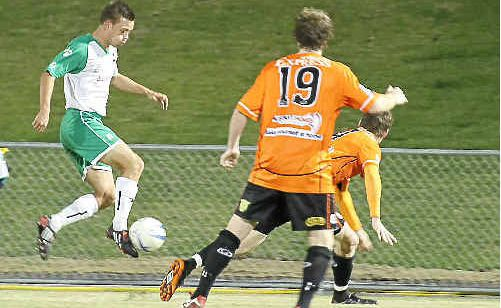 The Miners' Jamie Hatch on the ball as FNQ Bulls players, including Nathan Davies (19), look on.
