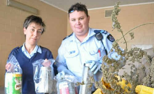Constable Jade Fleming and Senior Constable Jeremy Lambert with the drugs seized from two addresses last week.