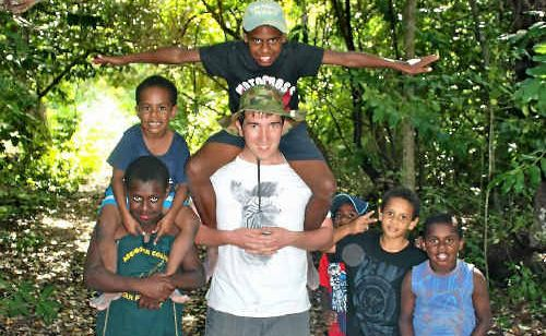 (Left) Mackay Christian College Year 11 student Daniel Fehring playing with local Torres Strait students on the island of Poruma. (Top right) A child models an outfit made by the MCC Year 9 Home Economics students. (Bottom right) MCC Year 11 students Josiah Westbrook and Rosie Fyvie enjoy games with some of the local children on Poruma.