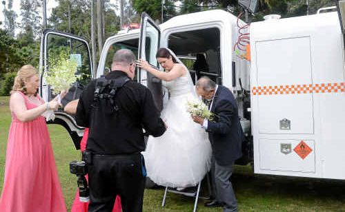 Rebecca Cutmore, helped by driver Athol Dorrington, steps down a ladder from a SES truck as bridesmaid Tracey Glasson looks on.