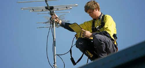 Better Lifestyles antenna installer Taylor Archer checks a TV antenna installed on a rooftop.