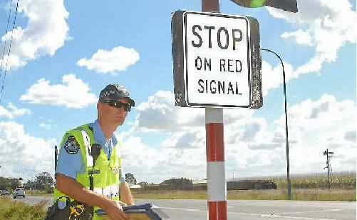 Mackay police Senior Constable Wyatt Telford monitors drivers at a rail crossing on the Peak Downs Highway at Racecourse yesterday.