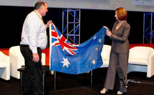 Prime Minster Julia Gillard presenting Lockyer Valley mayor Cr Steve Jones with the mud-streaked Australian flag salvaged from Grantham after the January floods.