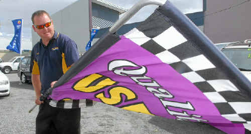 A BIT BREEZY: Ross Newton Motors Mackay sales manager Mark Streeter rearranges the car yard flags yesterday to make the most of the strong winds.
