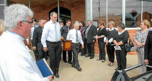 FINAL FAREWELL: Father Stephen Hanly (left) watches as pall bearers carry Bill Kemp's coffin through a guard of honour formed by former employees of Lambert's department store.