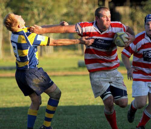 Redmen's Jono Speechley fends off a Southern Cross University opponent.