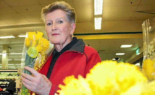 Cancer survivor Erin Kelly checks out daffodils for sale.