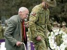 Battle of Milne Bay veteran Bert Miles (left) is escorted by Corporal Owen Bambrick to lay a wreath during the memorial service at the Mothers' Memorial to mark the 69th anniversary of the Battle of Milne Bay.