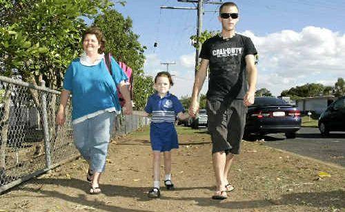 Bronwyn Welburn and her eldest son Aaron walk her youngest daughter from school yesterday.