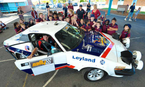 Troy and Penny O'Doherty show off their 1978 classic Triumph to kids at Coffs Harbour Primary School.