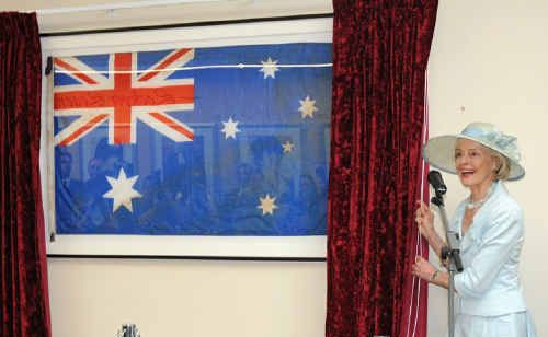 Quentin Bryce unveils the flag found among wreckage at Murphy's Creek