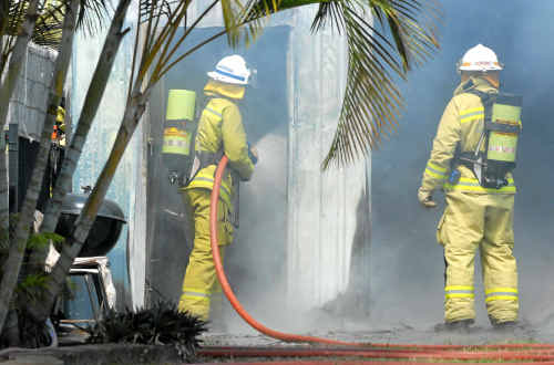 Queensland Fire and Rescue Service firefighters extinguish a fire that broke out in the garage of a Burwood Close home in Andergrove yesterday morning. It was the third fire in the region in 24 hours.