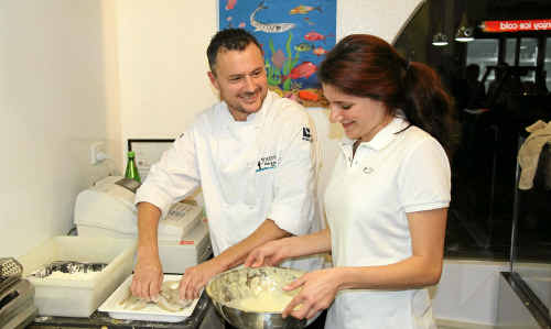 Wato's Fish and Burger Bar owner Tony Young prepares whiting fillets with the assistance of staff member Rhianna Jessup at the business's launch on Monday night.