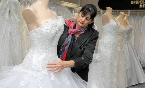 Jill Burston for Brides designer and fitter Jocelyn Fairbairn shows off a Brides Desire Gossamer style dress with corded metallic laces and feathers and Swarovski crystals. A traditional white dress, accompanied by a veil, is still the top pick for brides-to-be.