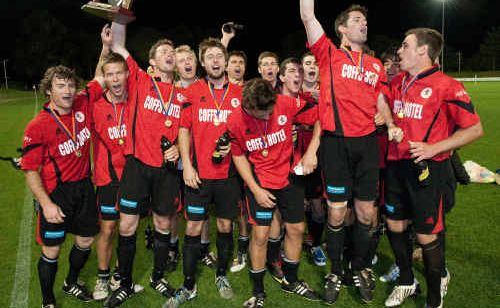 Coffs United players celebrate winning another men's first division grand final.