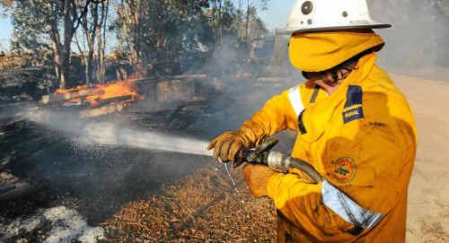 Bingera Weir Rural firefighter Darren Goodman-Jones keeps things under control as a small brush fire spreads through farm property.