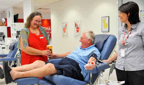 Volunteer Sandra Hopgood serves Warren Ross a milkshake under the watchful gaze of Australian Red Cross nurse Bec Albert.