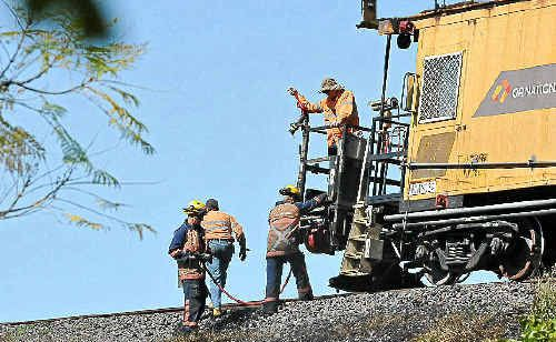 Rail workers put out grass fires caused by rail grinding work near the Grafton Bridge.