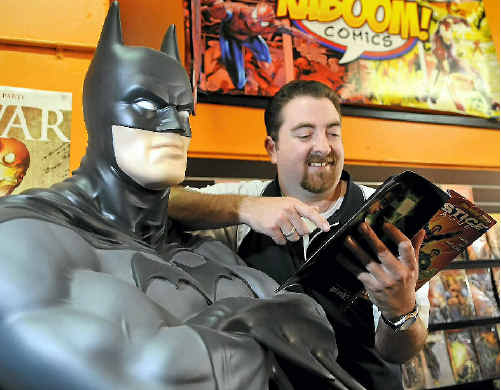 Kaboom comic bookshop owner Todd Baillie flicks through the new Justice League America comic with Batman.